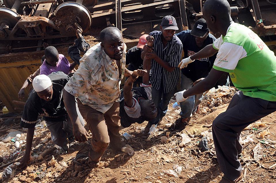 1) Жители трущоб Кибера в Найроби, Кения, несут тело, которое достали из-под обломков грузового поезда. Поезд сошел с рельс в понедельник, в результате чего двое погибли и несколько человек оказались в ловушке. Причины аварии пока неизвестны. (Simon Maina/Agence France-Presse/Getty Images)