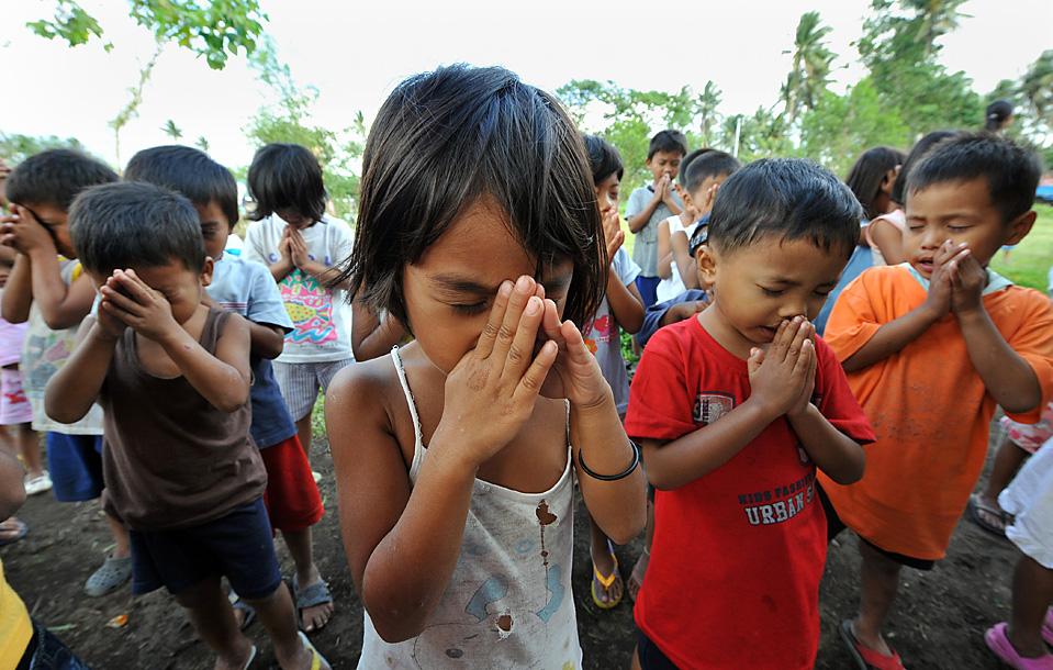 2) Дети эвакуированные из районов, расположенных у подножья вулкана Майон в Легаспи, Филиппины, молятся в своем временном приюте. Десятки тысяч людей были эвакуированы, поскольку вулкан Майон может перейти к самой активной стадии извержении. (Ted Aljibe/Agence France-Presse/Getty Images)