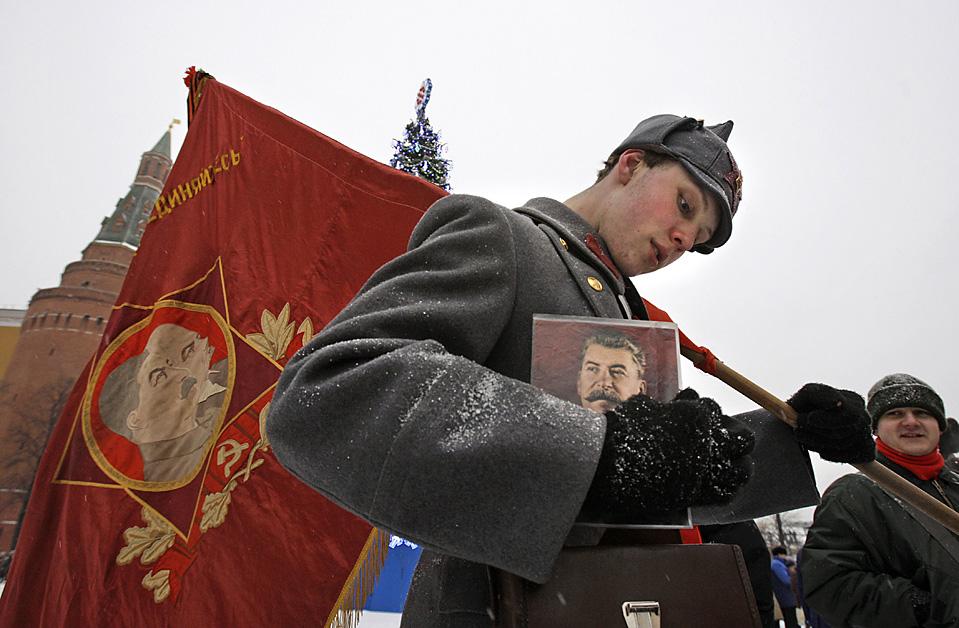 5) Молодой человек вынимает портрет Иосифа Сталина из сумки в ожидании начала церемонии возложения цветов на могилу Сталина на Красной площади. Церемония прошла по случаю 130-летия со дня рождения диктатора. (Alexander Zemlianichenko/Associated Press)