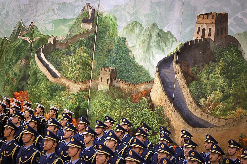 12) Почетный караул стоит по стойке смирно перед росписью Великой китайской стены во время церемонии встречи премьер-министра Франции Франсуа Фийона в Пекине. (Adam Dean/Bloomberg)